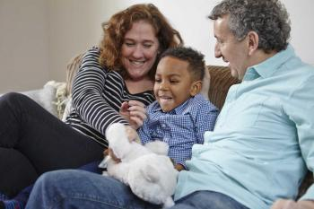 Adoptive parents with child on sofa