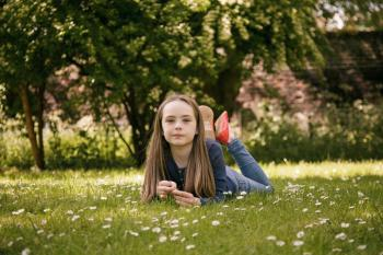 Young pre teen girl lying on grass in park