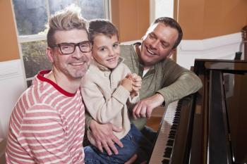 Two dads with their adopted son around a piano