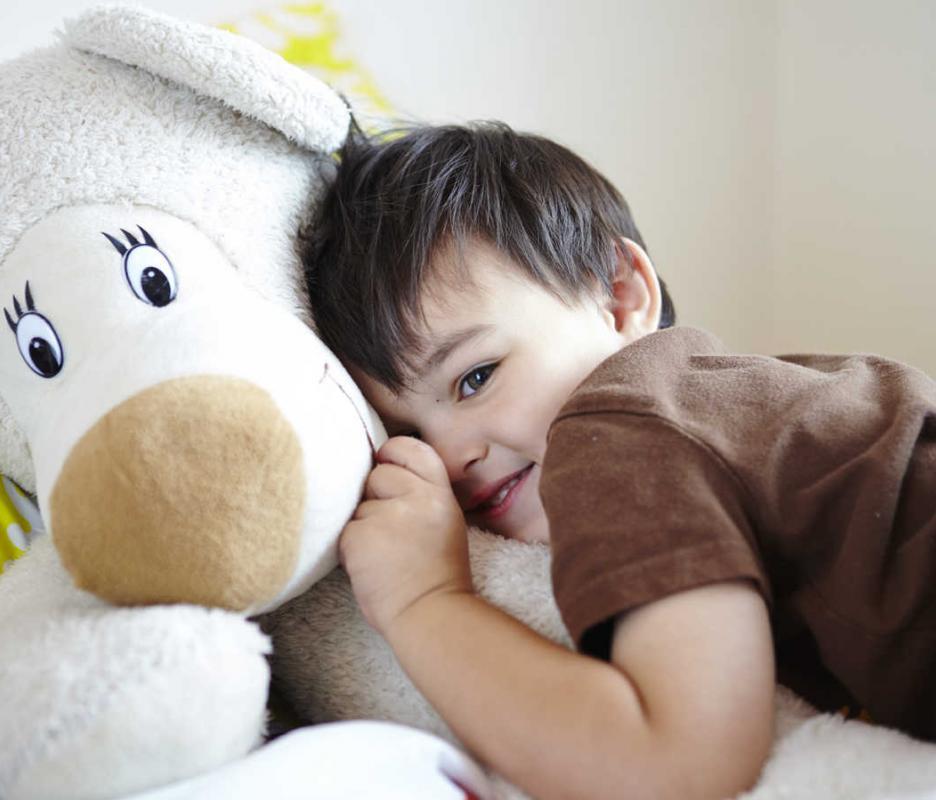 Boy cuddling teddy