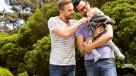 Happy adoptive dads outdoors with young child