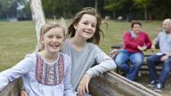 Two adopted girls having fun in the park with adoptive mum and dad in the background