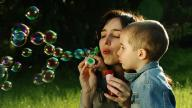 mother blowing bubbles with her son