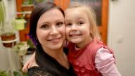 White mum smiling holding daughter