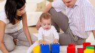 White Mum and Dad playing with baby girl and her toys