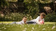 Brothers laying on grass with football