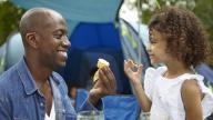 Black man and black girl picnic outside tent