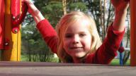 blonde girl on climbing frame