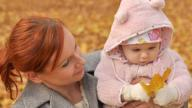 White mother and white baby girl playing outside in leaves