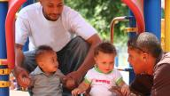 Black fathers with children playing in a playground