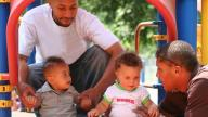 Two black dads with two young boys on play structure