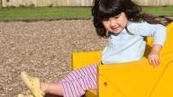 Girl going down yellow slide