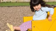 girl sitting in yellow playground toy