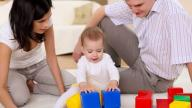 Baby playing with building blocks with couple