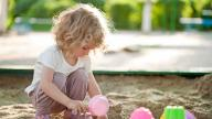blonde girl plays in sandpit