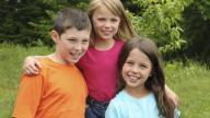 Three white siblings smiling