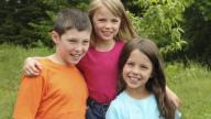 Three young white children in a garden
