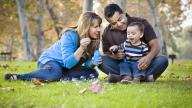 Parents sit with their son on the grass