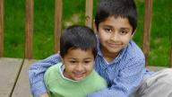 Two Indian brothers sitting in garden